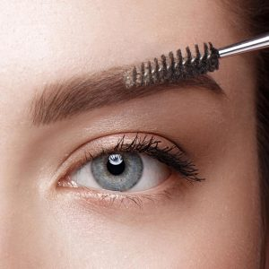 Close-up of female eyes with an eyebrow brush. Eye makeup cosmetics